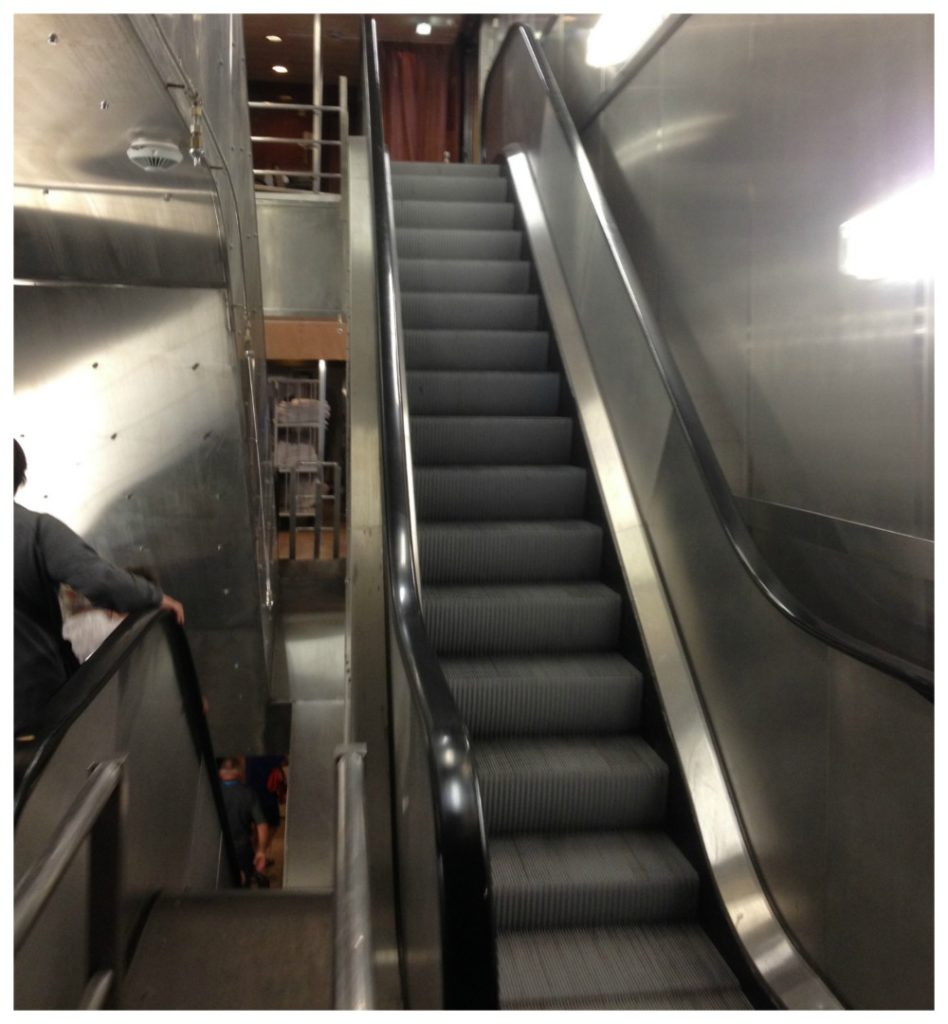 Two flights of moving stairs (escalators) down to the Galley