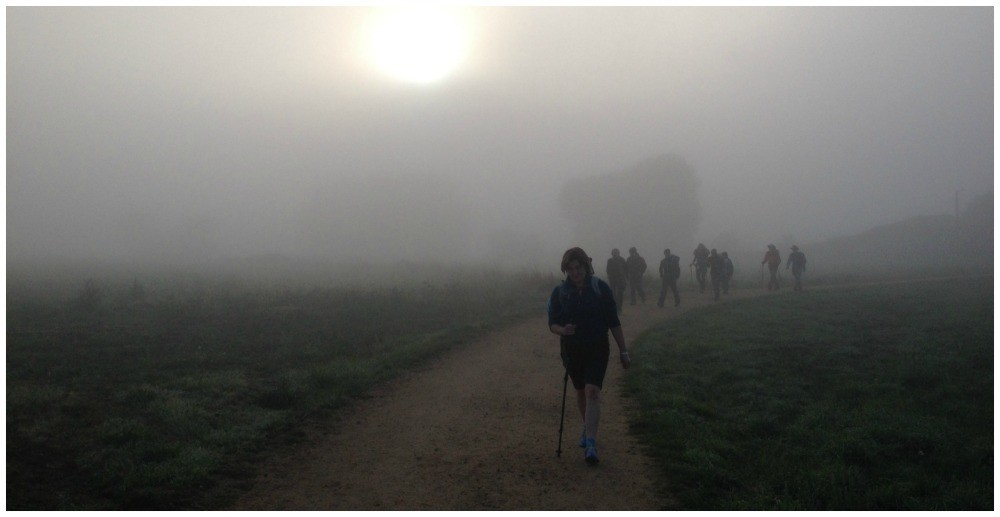 Pilgrims appear from the fog on the Camino leaving Sarria