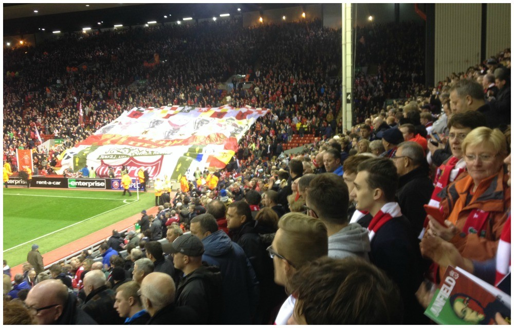 A huge flag being unwrapped at the Kop end